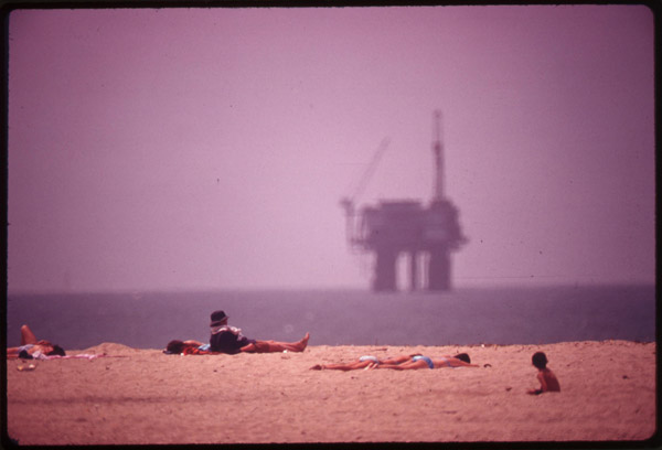 Sunbathers at Huntington Beach, and an oil platform offshore, May 1975 (Environmental Protection Agency)